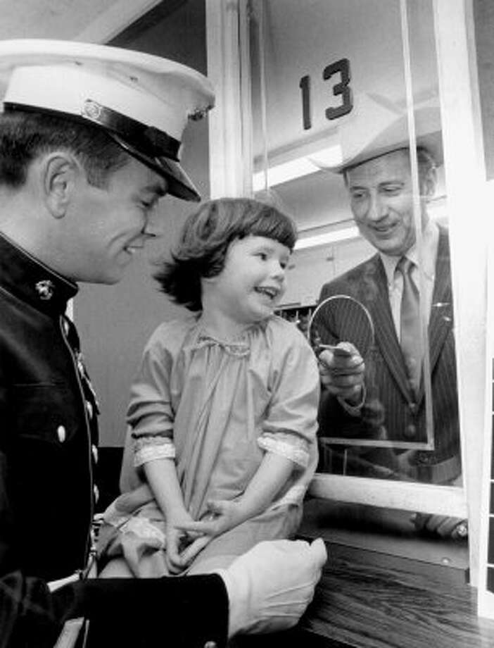 Show president Louis M. Pearce Jr. sells the first ticket to Karen Kay Chabysek, 4, daughter of Marine Maj. and Mrs. Herbert F. Chabysek Jr. With Karen is Marine Sgt. Michael Coine. (DARRELL DAVIDSON / HOUSTON CHRONICLE)