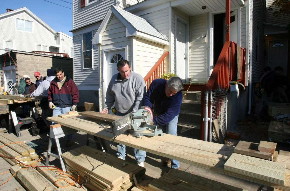 David Adams, center, of Design Buiders Inc. heads up a ramp project in Bridgeport with members of the Home Builders and Remodelers Association of Fairfield County Inc. The ramp is for Davina Martins, 6, who has cerebral palsy. Davina was not able to use a wheelchair at her home until the builders put in the ramp on Saturday, Nov. 7, 2009. St. Vincents Special Needs Services of Trumbull is also a partner in the project.