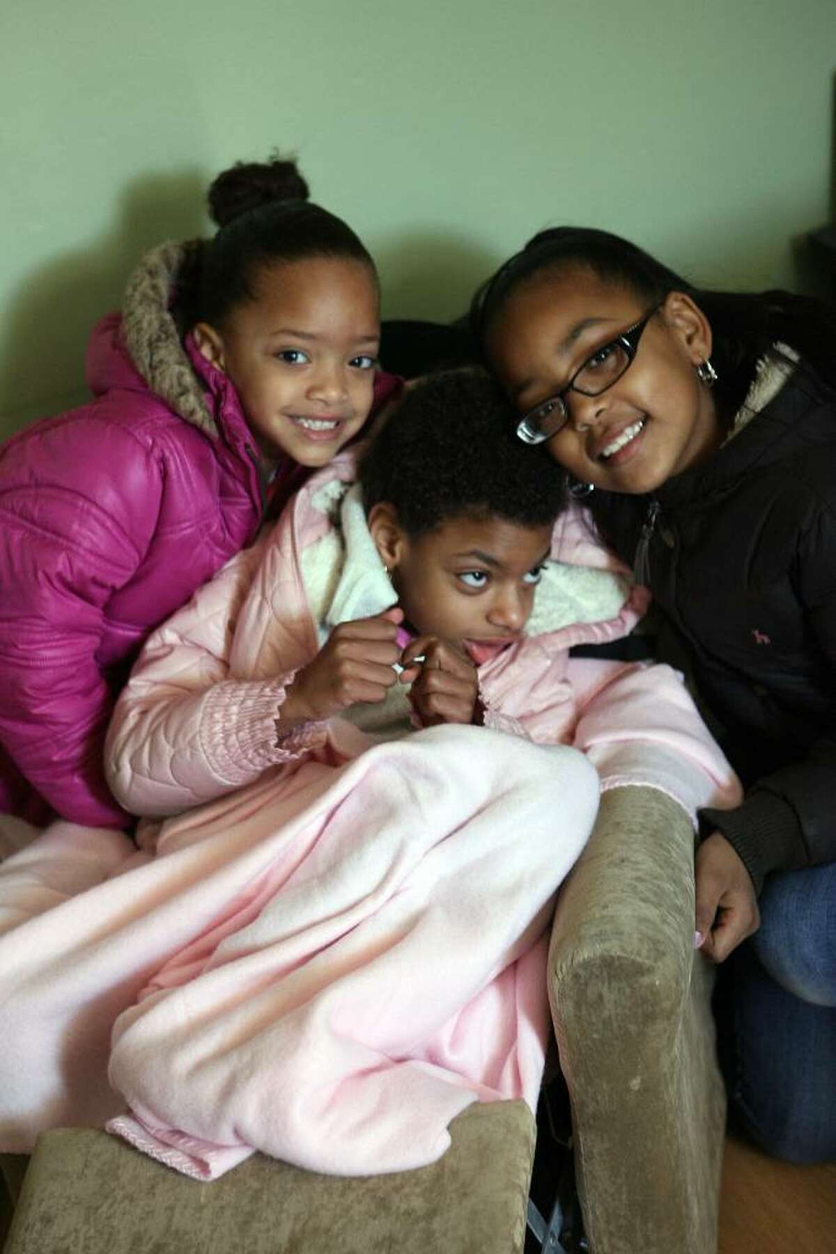 Davina Martins ,6 , center, poses with her sisters, Niki Martins,4 left, and Issa Dagraca in her Bridgeport home. Dave Adams of Design Builders and members of the Home Builders and Remodelers Association of Fairfield County Inc. partnered with St. Vincents Special Needs Services of Trumbull to build a ramp for Davina, who has cerebral palsy. Davina was not able to use a wheelchair at her home until the builders put in the ramp on Saturday, Nov. 7, 2009.