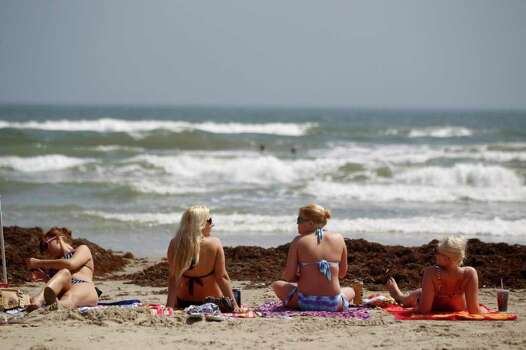 A group of spring breakers get some sun Tuesday, March 13, 2012 after the morning fog burned off on the beach in Port Aransas, Texas. (AP Photo/Corpus Christi Caller-Times, Michael Zamora) Photo: Associated Press