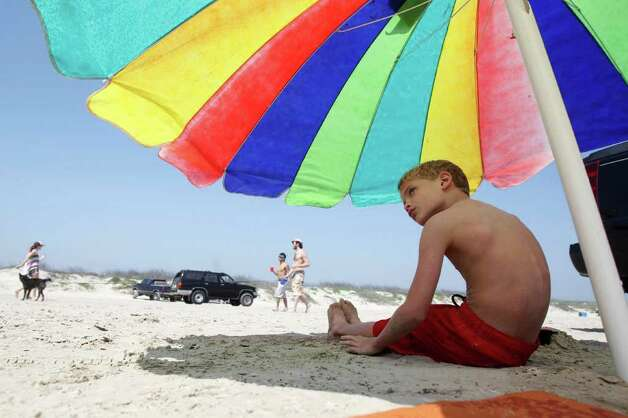 Grayson Slama, 7, of Austin, Texas, peaks out from under his beach umbrella Tuesday, March 13, 2012 on the beach in Port Aransas, Texas. (AP Photo/Corpus Christi Caller-Times, Michael Zamora) Photo: Associated Press