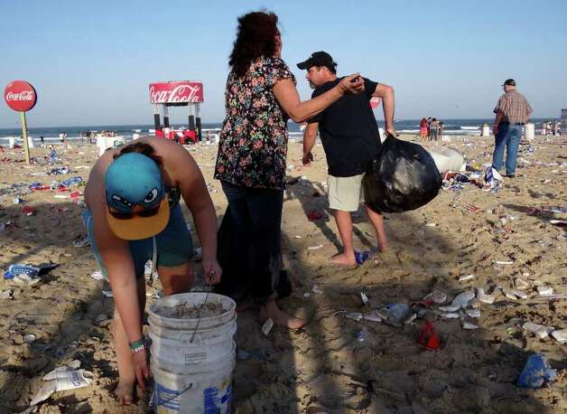 People clean trash on the South Padre Island Beach after an event during spring break on Tuesday, March 13, 2012. Billy Calzada / San Antonio Express-News Photo: Billy Calzada, San Antonio Express-News / San Antonio Express-News