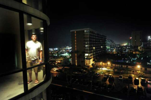 Mario Benavides stands behind a window at the Saida condominium on South Padre Island during spring break. Benavides, who hails from Los Fresnos, a city just a stone's throw from South Padre Island, brought 29 friends from college with him. He starred as a center on the University of Louisville football team. Billy Calzada / San Antonio Express-News Photo: Billy Calzada, San Antonio Express-News / San Antonio Express-News