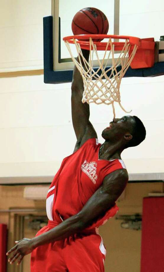 Lamar center Osas Ebomwonyi dunks during basketball practice, Tuesday, March 13, 2012, in Dayton, Ohio. Lamar plays Vermont on Wednesday in the first round of the NCAA college basketball tournament. (AP Photo/Al Behrman) Photo: Al Behrman, STF / AP
