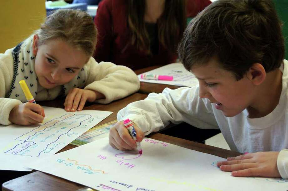 Pictured are Ox Ridge third grader Caroline Nemec, left, and fourth grader Matthew Fiorita making colorful posters about Pennies for Patients to publicize the campaign. Photo: Contributed Photo