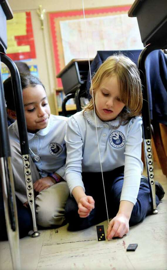 Hanna Newberry, right, and Ariana Pelletier, left, learn about pendulums and gravity at Grace Christian School in Stamford on Tuesday, March 6, 2012. Photo: Lindsay Niegelberg / Stamford Advocate