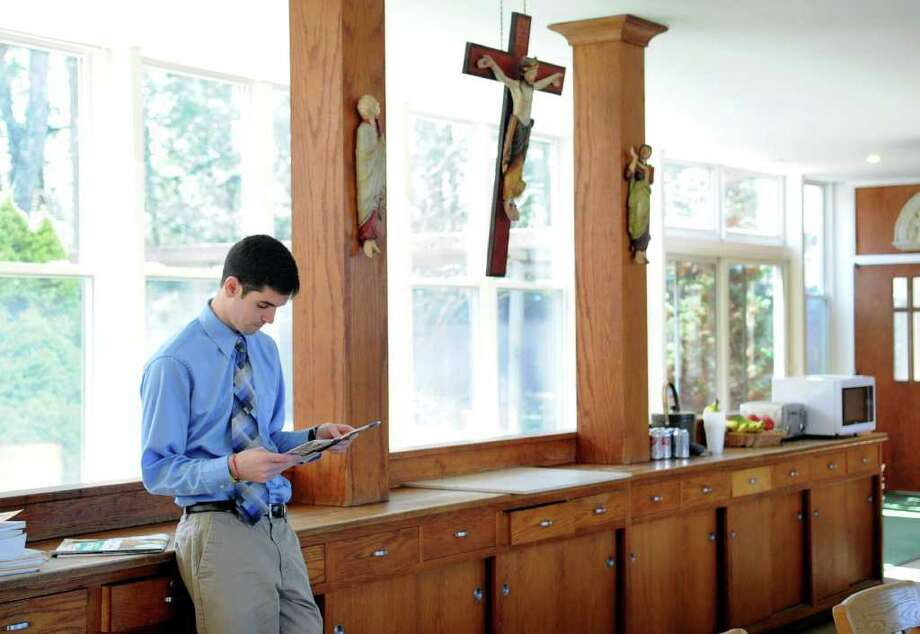 Seminarian Robert Nayden looks at a newspaper before spirituality class at St. John's Fisher Residence in Stamford on March 14, 2012. Photo: Lindsay Niegelberg / Stamford Advocate