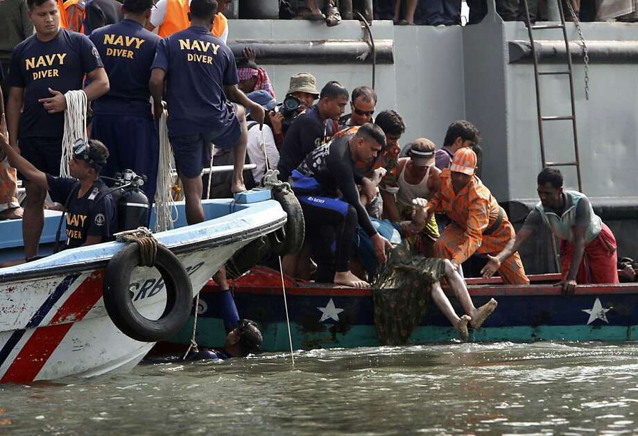 Rescuers recover the body of a victim of a ferry accident on the banks of the Meghna River in Munshiganj district, about 20 miles (32 kilometers) south of Dhaka, India, Tuesday, March 13, 2012. A ferry packed with about 200 people capsized in a river in southern Bangladesh on Tuesday, killing 31 people and leaving dozens more missing, authorities said. Photo: Pavel Rahman, Associated Press