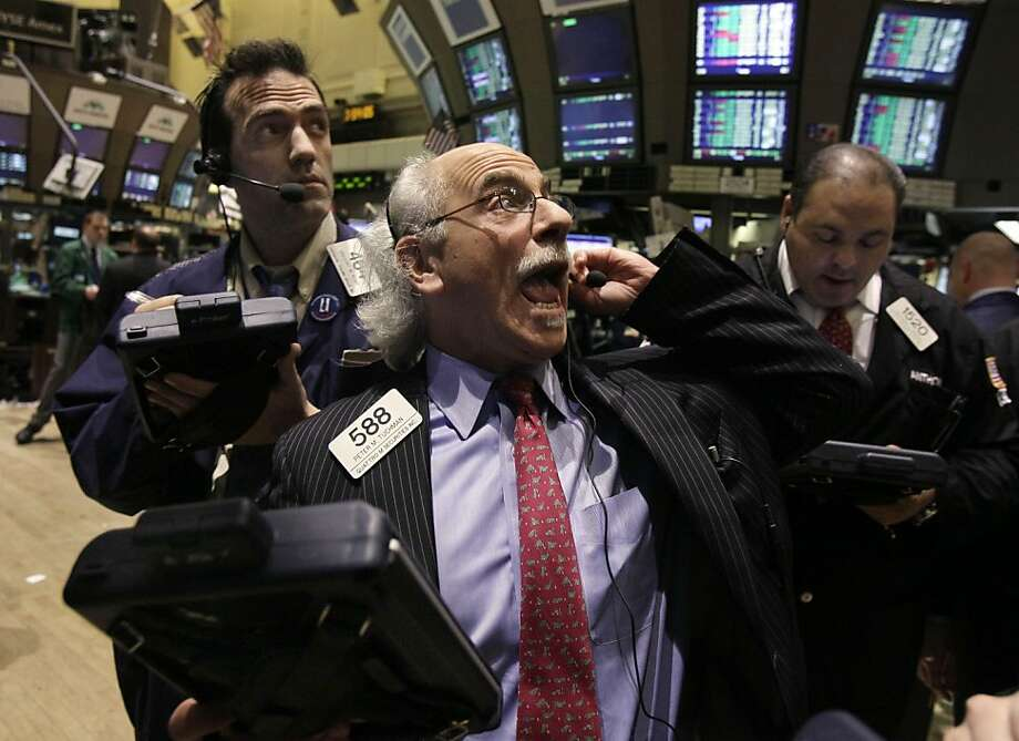 Trader Peter Tuchman, center, works on the floor of the New York Stock Exchange Tuesday, March 13, 2012. The Dow Jones industrial average rose 218 points and closed at its highest level since the end of 2007. (AP Photo/Richard Drew) Photo: Richard Drew, Associated Press