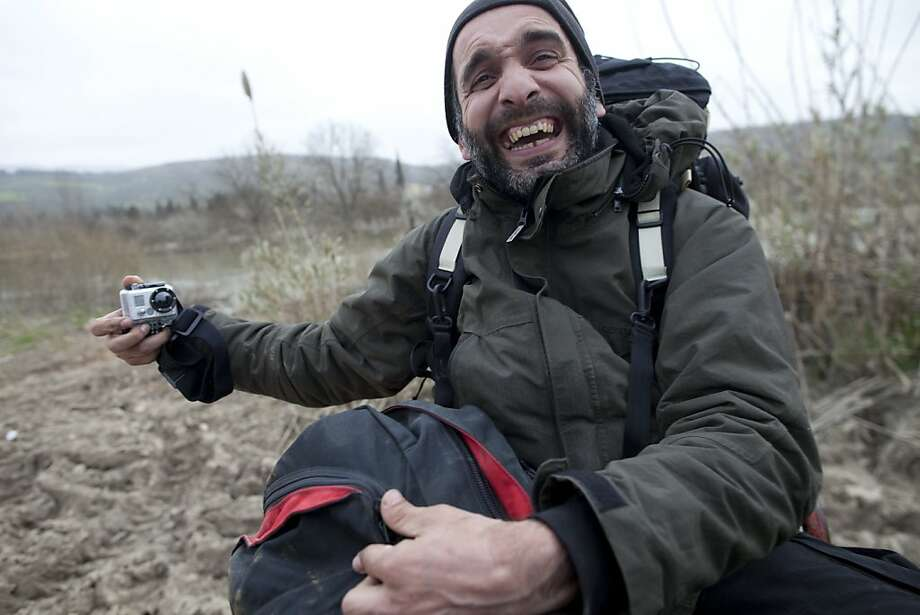 AP's Ahmed Bahaddou laughs while crossing back into Turkey after covering the violence in Syria for three weeks, Syria, Monday, March 12, 2012. Rodrigo Abd and Ahmed Bahaddou sneaked into Syria and spent nearly three weeks reporting from opposition-held territory. Abd, an Associated Press photographer, is based in Guatemala. Bahaddou is a freelance TV news producer, based in Turkey. Photo: Rodrigo Abd, Associated Press