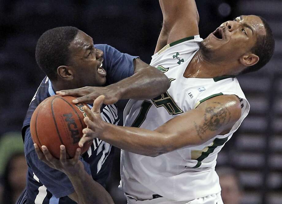 Villanova forward JayVaughn Pinkston, left, runs into South Florida forward Ron Anderson Jr. as he drives to the basket during the first half of an NCAA college basketball game Wednesday, Feb. 15, 2012, in Tampa, Fla. (AP Photo/Chris O'Meara) Photo: Chris O'Meara, Associated Press