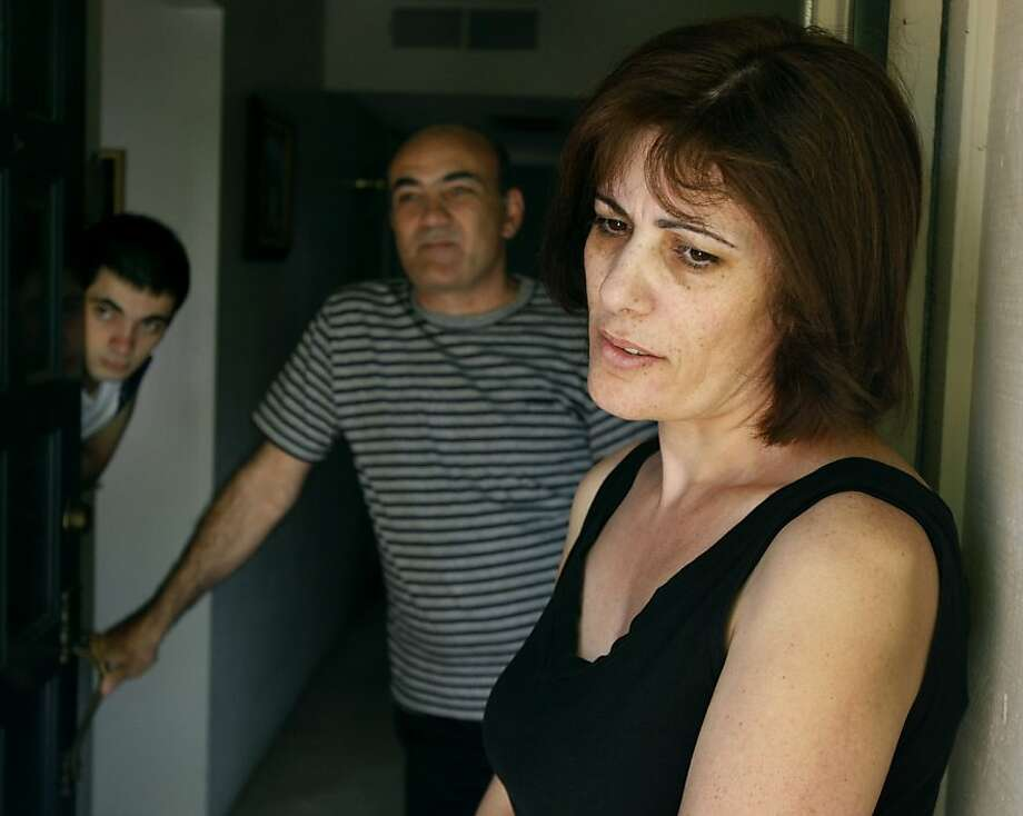Asmik Karapetian, right, her husband Ruben, and son Arthur meet with a neighbor at their home in Fresno, Calif. Photo by Paul Chinn / The Chronicle Photo: Paul Chinn, The Chronicle