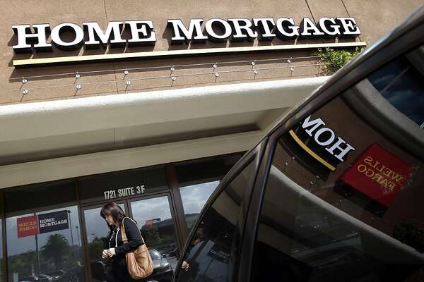 A woman walks past a Wells Fargo Home Mortgage office in La Habra, Calif., Thursday, Oct. 7, 2010. Rates on 30-year mortgages  fell to a new low for the ninth time in 12 weeks, pushed down by traders anticipating a likely move by the Federal Reserve to pump more money into the economy.
