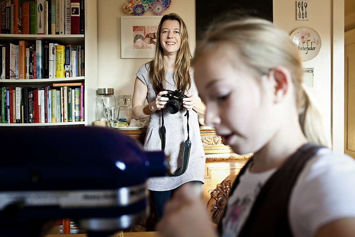 Phyllis Grant photographs her daughter Bella, 9, as she helps mix dough to make chocolate chip cookies as part of a cooking segment for her blog, dashandbella.blogspot.com, at their home in Berkley, Calif., March 6, 2012. Jason Henry/Special to The Chronicle