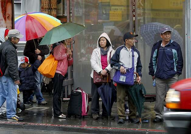 An overflow crowd waited in a Stockton Street bus stop at noon. In San Francisco's Chinatown, a steady rain didn't stop natives and visitors from getting out on the streets and shopping or visiting restaurants Tuesday March 13, 2012. Photo: Brant Ward, The Chronicle