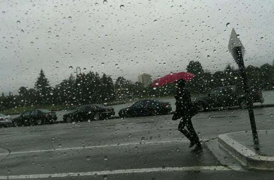 A pedestrian walks in the rain along Lake Merritt in Oakland on Tuesday afternoon, March. 13, 2012. Photo: Trish Gervasio, Courtesy To The SF Gate