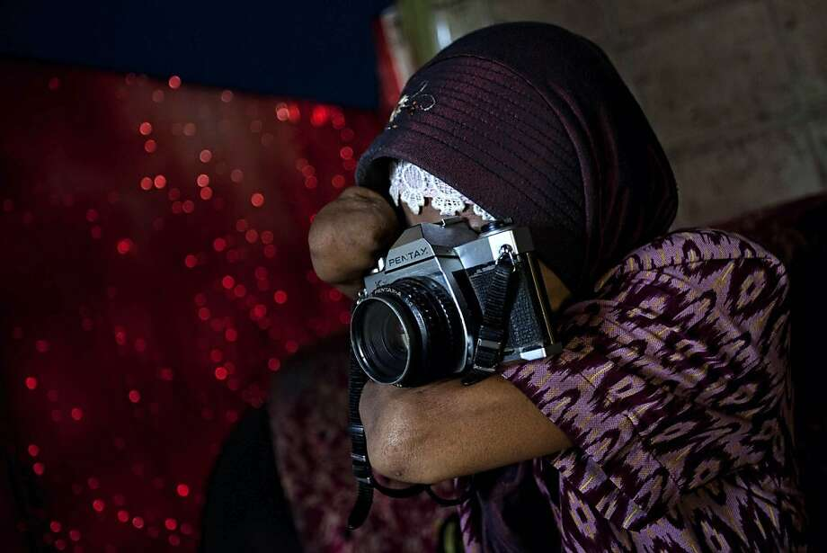 PURWOREJO, INDONESIA - MARCH 13:  Armless professional photographer Rusidah, 44, takes a photograph as she carries out camera maintenance on March 13, 2012 in Purworejo, Indonesia. Rusidah shoots weddings and parties and has a small studio at home in the village of Botorejo, Bayan District, Purworejo, Central Java where her husband and son also reside. She has been in the photography business for nearly 20 years.  (Photo by Ulet Ifansasti/Getty Images) Photo: Ulet Ifansasti, Getty Images