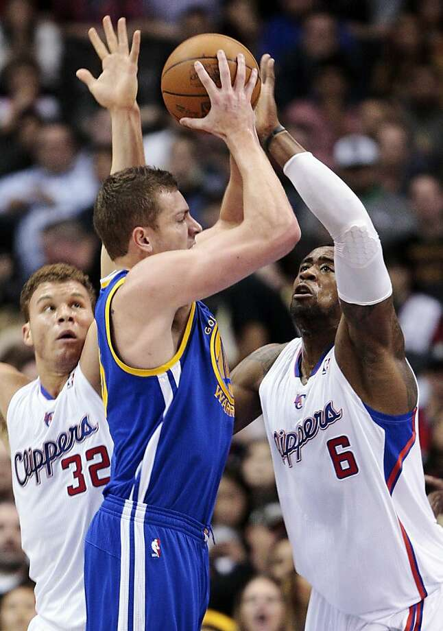 Golden State Warriors' David Lee, center, shoots between Los Angeles Clippers' Blake Griffin (32) and DeAndre Jordan (6) defend in the first half of an NBA basketball game, Sunday, March 11, 2012, in Los Angeles. (AP Photo/Jason Redmond) Photo: Jason Redmond, Associated Press