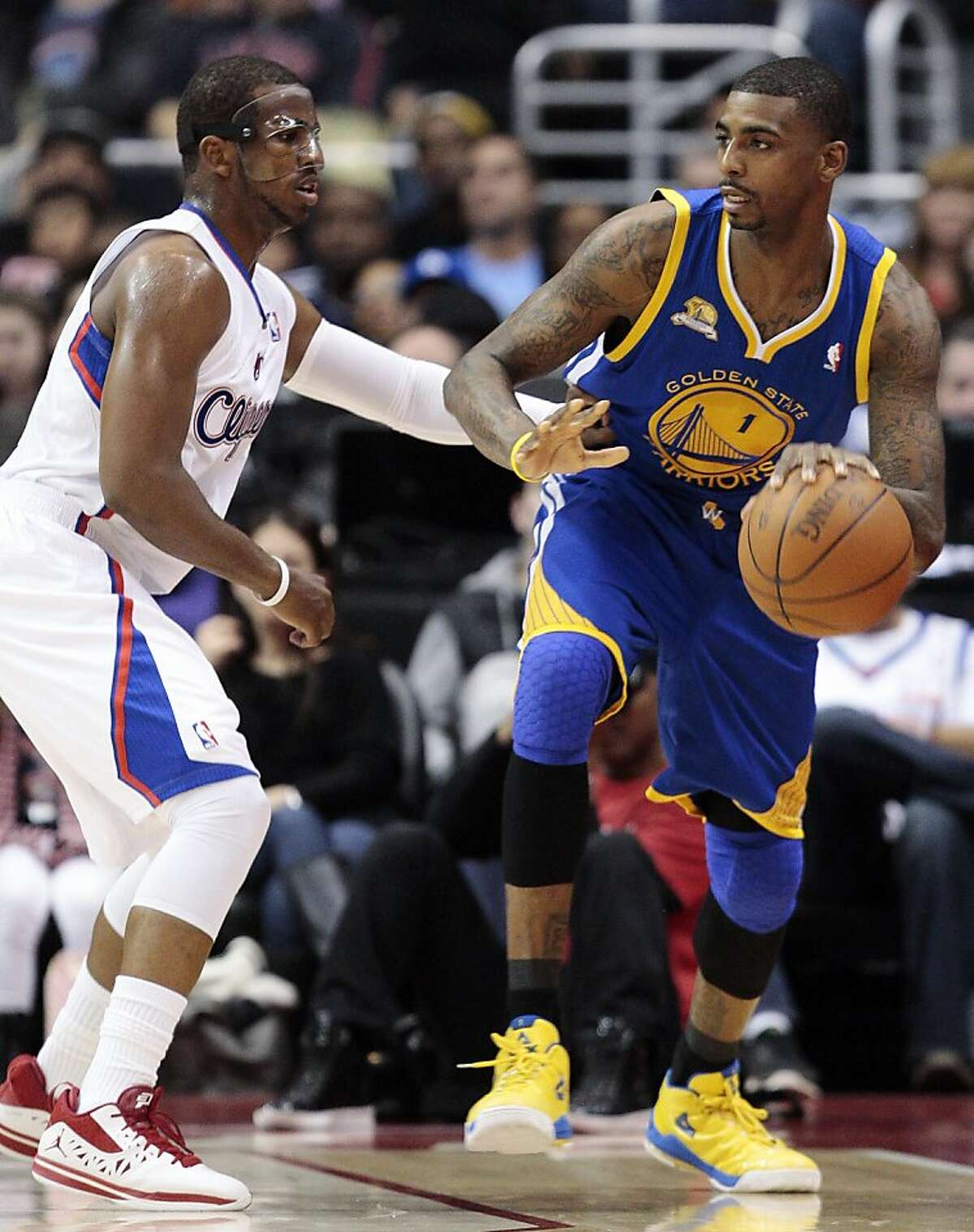 Golden State Warriors forward Dorell Wright, right, moves the ball as Los Angeles Clippers' Chris Paul defends in the first half of an NBA basketball game, Sunday, March 11, 2012, in Los Angeles. (AP Photo/Jason Redmond)