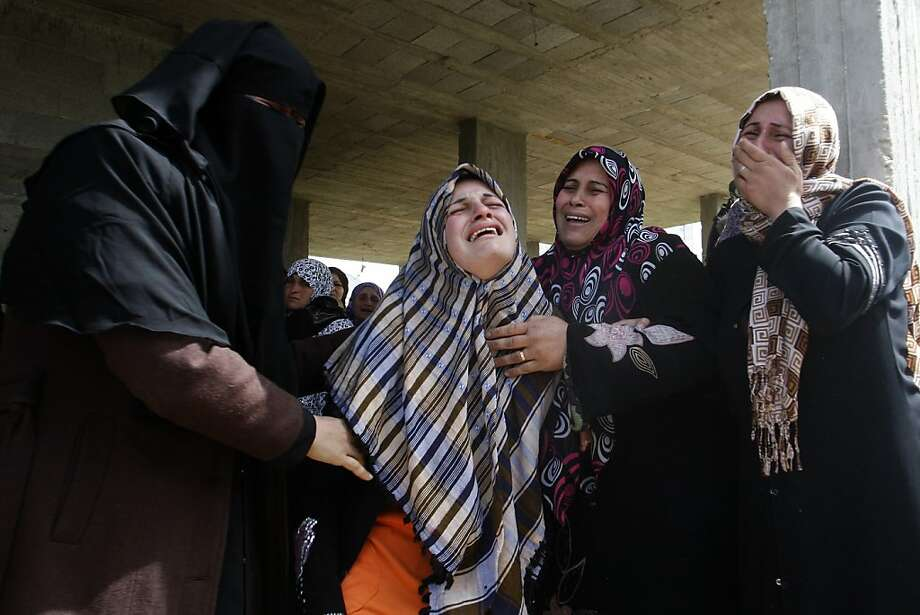 Palestinians women react during the funeral of 12 year old Ayoub Assalya killed in an Israeli airstrike in Jabaliya Refugee Camp, Gaza Strip, Sunday, March 11, 2012. The worst round of violence in more than a year between Israel and Gaza Strip Palestinians deepened Sunday with deadly Israeli airstrikes and a barrage of rockets fired into the Jewish state. (AP photo/Hatem Moussa) Photo: Hatem Moussa, Associated Press