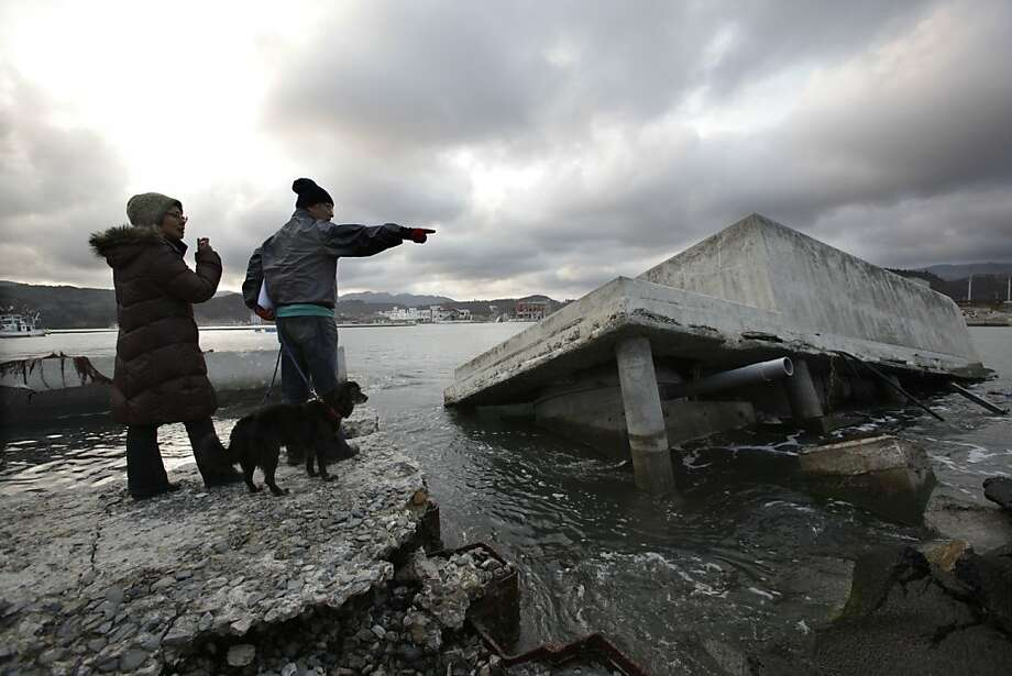 Nobuo Watanabe, right, and his wife, Seiko, with their dog look at a breakwater badly damaged by the last year's earthquake and tsunami in Minamisanriku, Miyagi Prefecture, Sunday, March 11, 2012. People across Japan prayed and stood in silence on Sunday to remember the massive disaster that struck the nation one year ago, killing just over 19,000 people and unleashing the world's worst nuclear crisis in a quarter century. (AP Photo/Shizuo Kambayashi) Photo: Shizuo Kambayashi, Associated Press