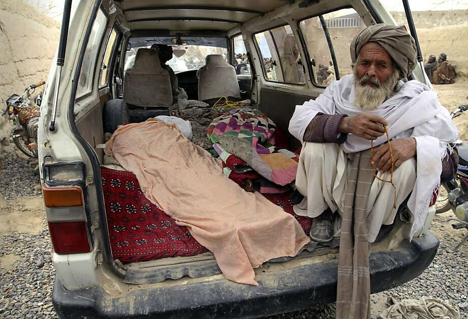 An elderly Afghan man sits next to the covered body of a person who was allegedly killed by a U.S. service member, in a minibus in Panjwai, Kandahar province south of Kabul, Afghanistan, Sunday, March 11, 2012. A U.S. service member walked out of a base in southern Afghanistan before dawn Sunday and started shooting Afghan civilians, according to villagers and Afghan and NATO officials. Villagers showed an Associated Press photographer 15 bodies, including women and children, and alleged they were killed by the American. (AP Photo/Allauddin Khan) Photo: Allauddin Khan, Associated Press