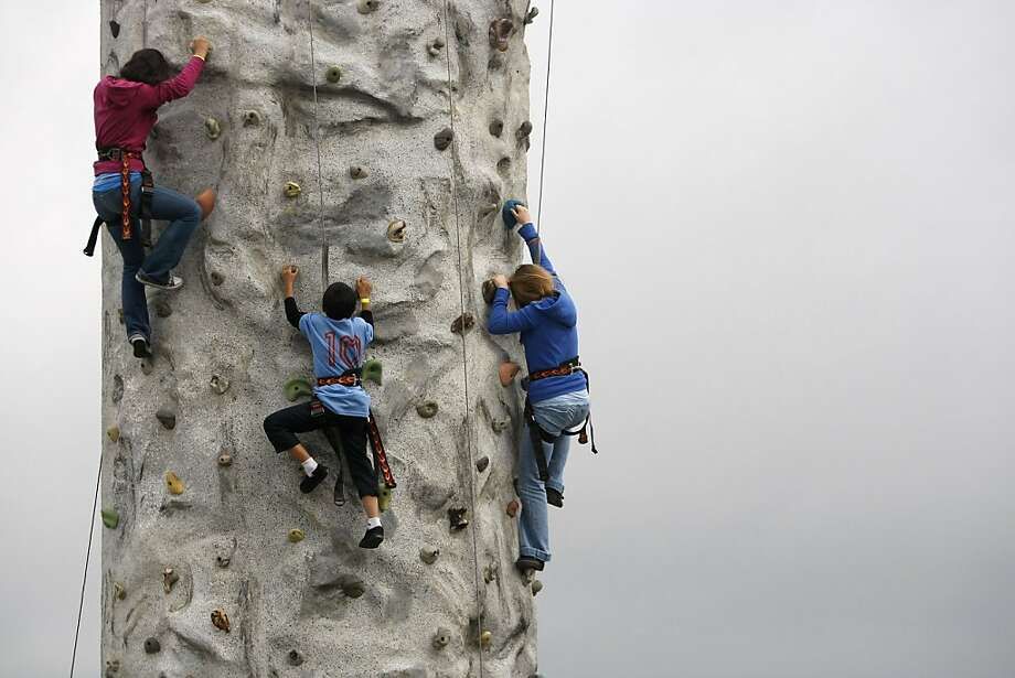 Three kids have a race to the top of the rock climbing wall by Pier 39. San Francisco started its annual Sunday Streets neighborhood street fairs on Sunday, March 11, 2012, by closing automotive traffic on Embarcadero Street from Howard Street down to the Fisherman's Wharf for runners, bicyclists, and anyone else to enjoy. Photo: Sean Culligan, The Chronicle