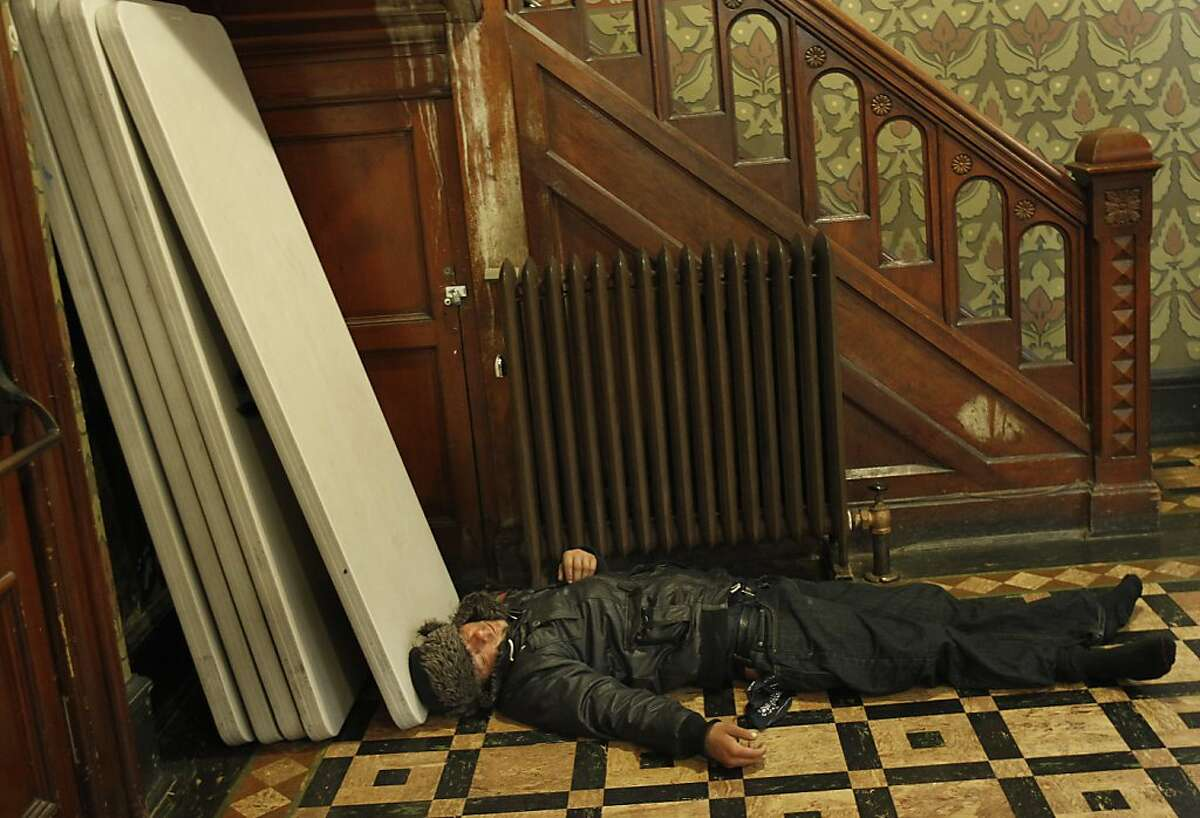 A man who didn't find room in the pews, slept on the floor at the rear of the church. The Gubbio project at St. Boniface Church in San Francisco, Calif. has seen an increase in homeless since the Transbay Terminal was demolished and the sit/lie ordinance enforced. The Gubbio project allows people to sit and sleep in the pews of the Tenderloin Catholic church from 6 a.m. til 1 p.m.