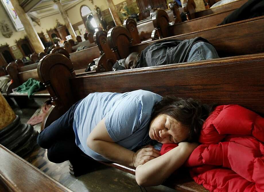 Julieanne Fernandez, 51, stretched out in her pew for some needed rest. The Gubbio project at St. Boniface Church in San Francisco, Calif. has seen an increase in homeless since the Transbay Terminal was demolished and the sit/lie ordinance enforced. The Gubbio project allows people to sit and sleep in the pews of the Tenderloin Catholic church from 6 a.m. til 1 p.m. Photo: Brant Ward, The Chronicle