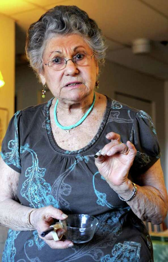 Gloria Blick, 90, holds a small amount of marijuana rolled into a joint, which she calls a cigarette, in her Stamford apartment on Wednesday, February 14, 2012. Blick suffers from glaucoma and uses two puffs of marijuana before bed each night to ease the pressure inside her eyes and prevent blindness. Photo: Lindsay Niegelberg / Stamford Advocate