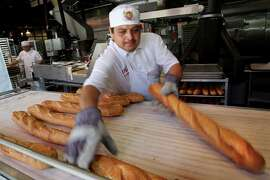Baker Hugo Hernandez removed hot baguettes from the oven at Boudin Bakery on Fisherman's Wharf on April 20, 2008 in San Francisco, Calif.