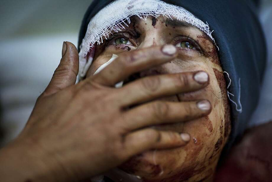In this Saturday, March 10, 2012 photo, Aida cries as she recovers from severe injuries after the Syrian Army shelled her house in Idlib, north Syria. Aida's husband and two of her children were killed after their home was shelled. (AP Photo/Rodrigo Abd) Photo: Rodrigo Abd, Associated Press