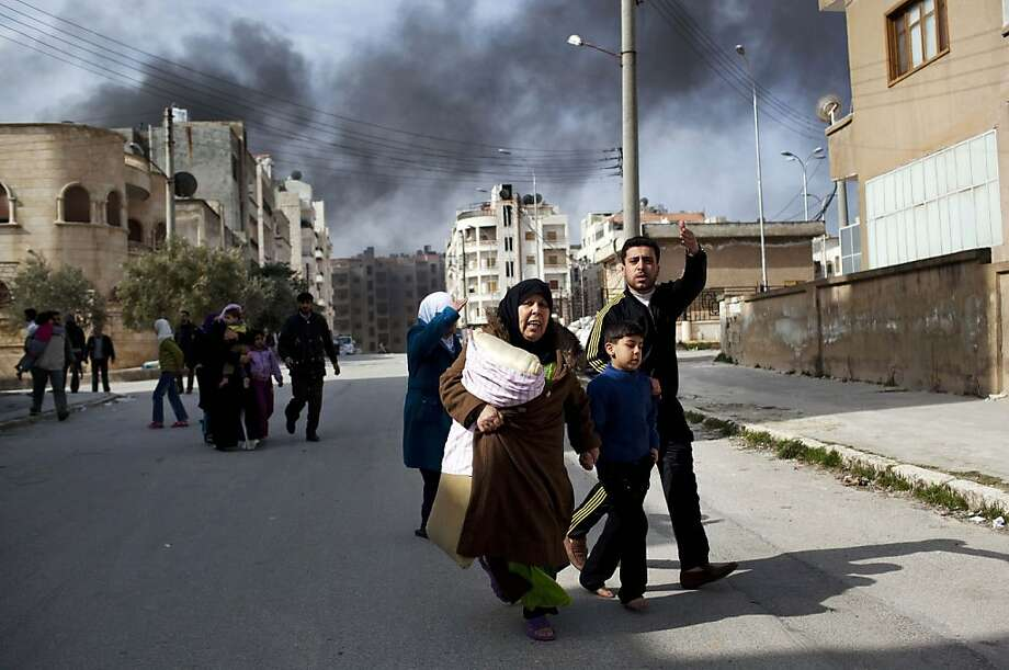 A family escapes from fierce fighting between Free Syrian Army fighters and government troops in Idlib, north Syria, Saturday, March 10, 2012. U.N. envoy Kofi Annan met with Syrian President Bashar Assad on Saturday in Damascus during a high-profile international mission to mediate an end to the country's yearlong conflict. Photo: Rodrigo Abd, Associated Press