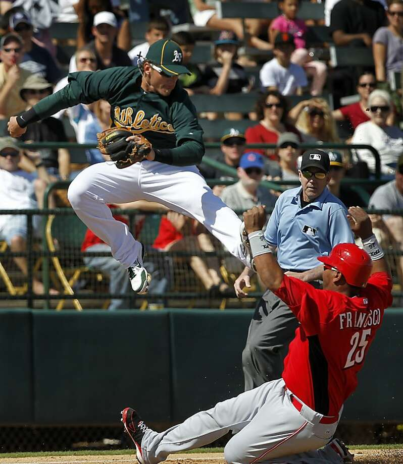 Cincinnati's Juan Francisco slides into third with a stolen base under Josh Donaldson, who had to leap to prevent the ball from going into left field, in the 2nd inning of the Oakland A's Cactus League spring training game against the Reds in Phoenix, Ariz. on Saturday, March 10, 2012. Photo: Paul Chinn, The Chronicle
