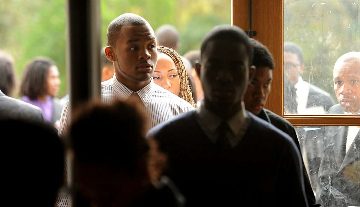 Jazmin Ridley waits with other Afrikan Black Coalition Conference attendees to pass through a metal detector for Nation of Islam Minister Louis Farrakhan's speech on Saturday, March 10, 2012, in Berkeley, Calif. Ridley is a student at the University of California, Davis.