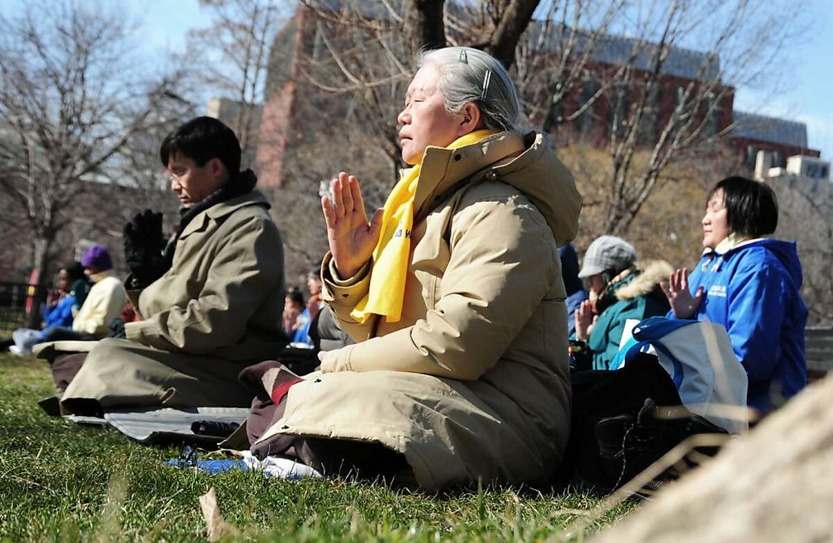 Falun Gong practitioners meditate during a pro-Tibetan demonstration February 14, 2012 in Lafayette Park across from the White House in Washington, DC. As Chinese Vice President Xi Jinping and US President Barack Obama held talks at the White House, dozens of impassioned pro-Tibet and anti-Chinese government activists outside meditated, waved flags and chanted