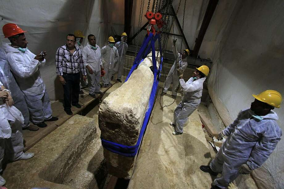In this Thursday, June 23, 2011 file photo, an Egyptian and Japanese team of scientists use a pulley system to lift the first of 41 16-ton limestone slabs to reveal fragments of the ancient ship of King Khufu next to the Great Pyramid of Giza, Egypt. Archaeologists began a second-phase of restoration work on a 4,500-year-old wooden boat found next to the Great Pyramid of Giza, one of Egypt's main tourist attractions. (AP Photo/Khalil Hamra, File) Photo: Khalil Hamra, Associated Press