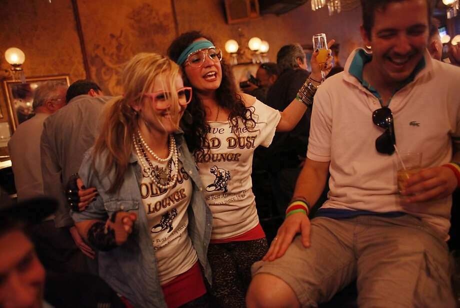 On the day the the owners of the Gold Dust Lounge were supposed to leave, Katie Walker and Lucia Cifonelli, of San Francisco, celebrate that fact that the Gold Dust Lounge is staying for the time being on March 10, 2012 in San Francisco, Calif. Photo: Mike Kepka, The Chronicle
