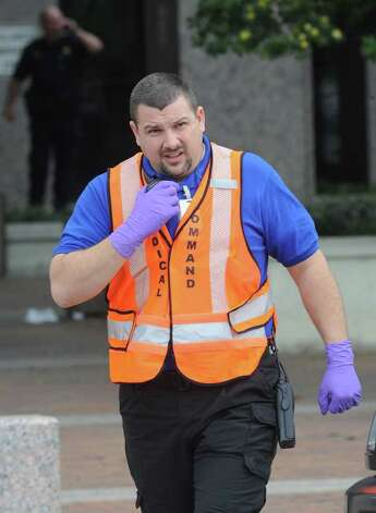 A paramedic rushes toward the Jefferson County Courthouse on Wednesday after a shooting that left one person dead and several people injured.  Photo taken Wednesday, March 13, 2012  Guiseppe Barranco/The Enterprise Photo: Guiseppe Barranco, STAFF PHOTOGRAPHER / The Beaumont Enterprise