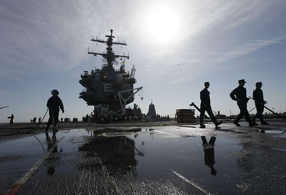 In this March 8, 2012 photo, sailors clean the flight deck as they move supplies and equipment in preparation for the final deployment of the nuclear aircraft carrier USS Enterprise at the Norfolk Naval Station in Norfolk, Va. The ship's storied 50-year history includes action in several wars, a prominent role in the Cuban missile crisis and serving as a spotter ship for John Glenn's orbit of the Earth. Photo: Steve Helber, Associated Press