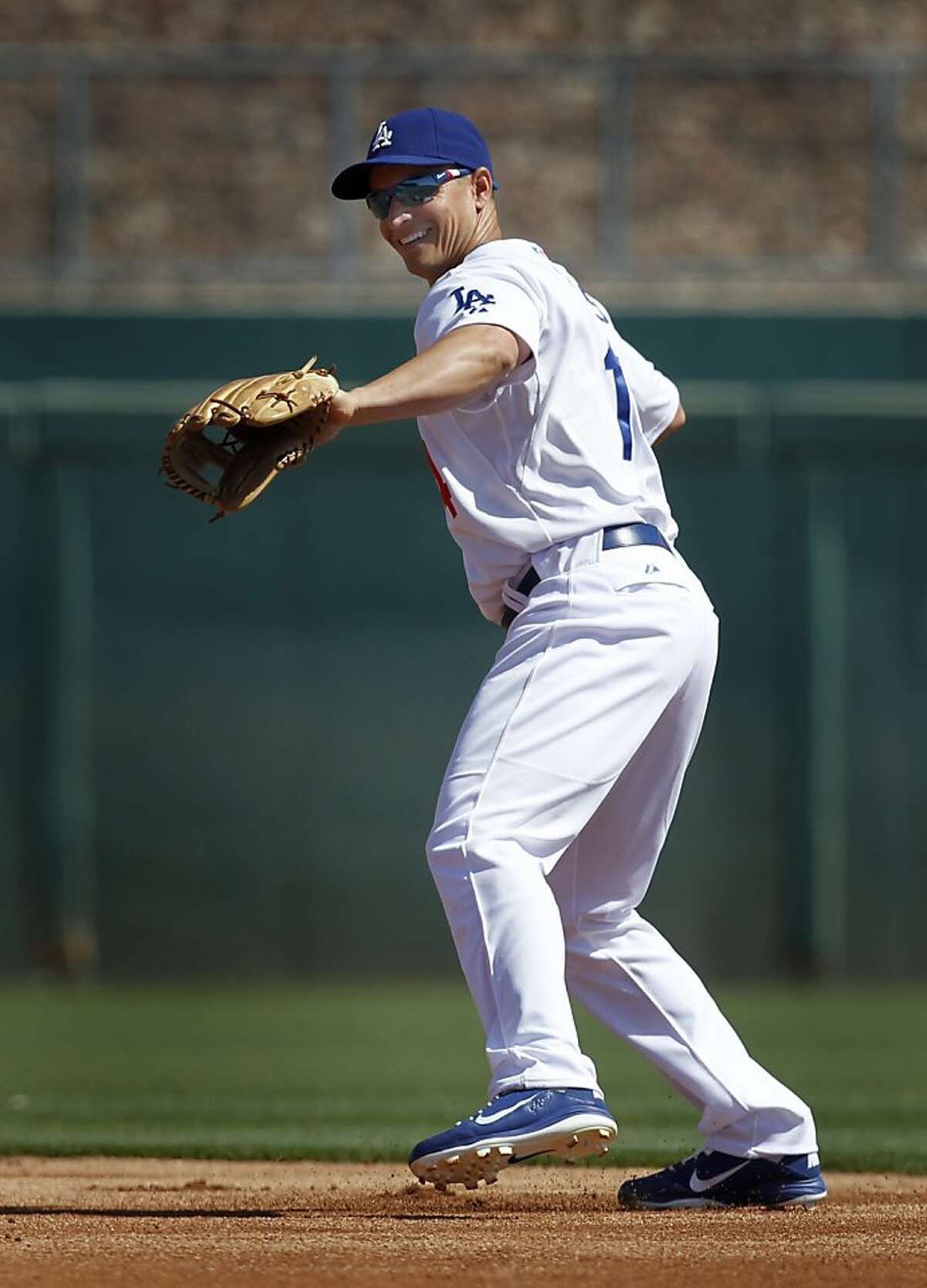 Former Oakland second baseman Mark Ellis warms up in the 1st inning of the A's Cactus League spring training game against the Los Angeles Dodgers in Glendale, Ariz. on Thursday, March 8, 2012.
