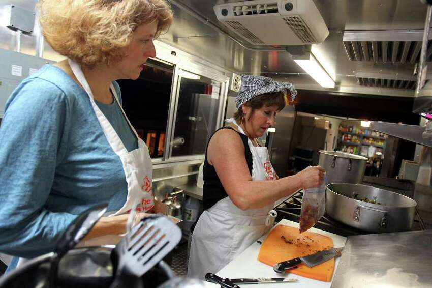 Volunteer Elaine Olivier and founder/ chef Joan Cheever prepare dinner for service before the Chow Train feeds the homeless in partnership with Resurrection Ministries at several stops around San Antonio.