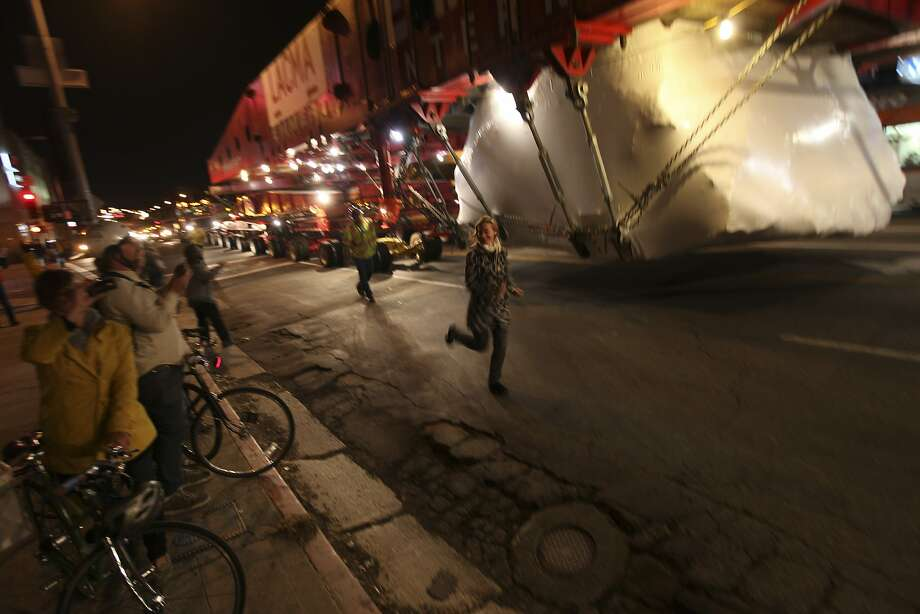 """A woman jogs beside the artwork """"Levitated Mass"""" as it nears its destination in Los Angeles, March 10, 2012. After 11 days and through 22 cities, the 340-ton, 21-foot-high rock-turned-art known as """"Levitated Mass"""" arrived at the Los Angeles County Musuem of Art around 4:35 a.m. on Saturday. Photo: Monica Almeida, New York Times"""