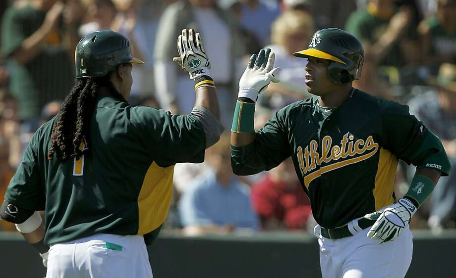 Manny Ramirez welcomes Yoenis Cespedes back to the dugout after Cespedes' 4th inning home run in the Oakland A's spring training game against the Cincinnati Reds in Phoenix, Ariz. on Saturday, March 10, 2012. Cespedes went 2-for-2, with a walk, single and the homer in his Cactus League debut. Photo: Paul Chinn, The Chronicle