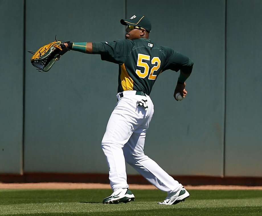 Center fielder Yoenis Cespedes fields a single by Juan Francisco in the 2nd inning of the Oakland A's spring training game against the Cincinnati Reds in Phoenix, Ariz. on Saturday, March 10, 2012. Cespedes went 2-for-2, with a walk, single and home run in his Cactus League debut. Photo: Paul Chinn, The Chronicle