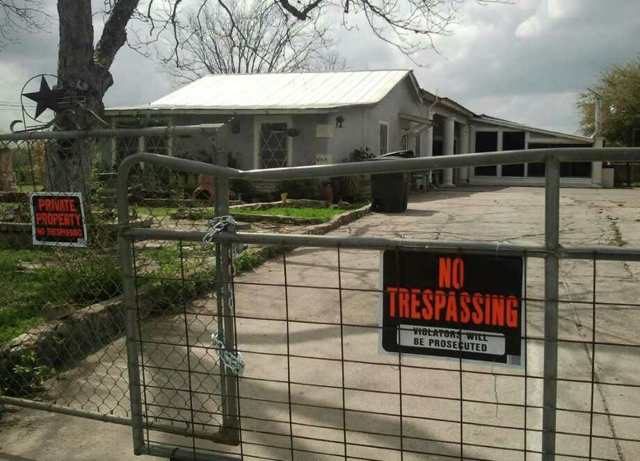 Warning signs have been posted on the fence of a home on the South Side where 20 undocumented immigrants were found in a raid on March 10. Photo: Guillermo Contreras, San Antonio Express-News