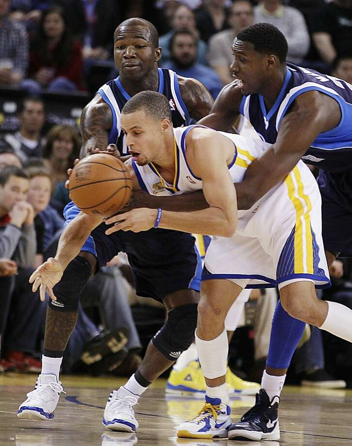 Dallas Mavericks' Dominique Jones, left, and Ian Mahinmi, right, strip the ball from Golden State Warriors' Stephen Curry during the first half of an NBA basketball game, Saturday, March 10, 2012, in Oakland, Calif. (AP Photo/Ben Margot) Photo: Ben Margot, Associated Press