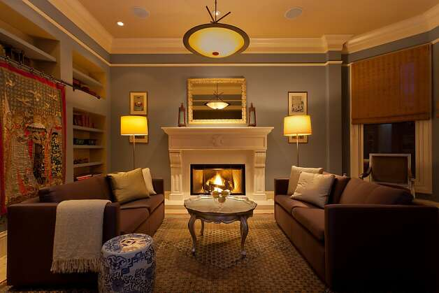 Featuring a fireplace, the family room also has crown molding and large windows. Photo: Reflex Imaging