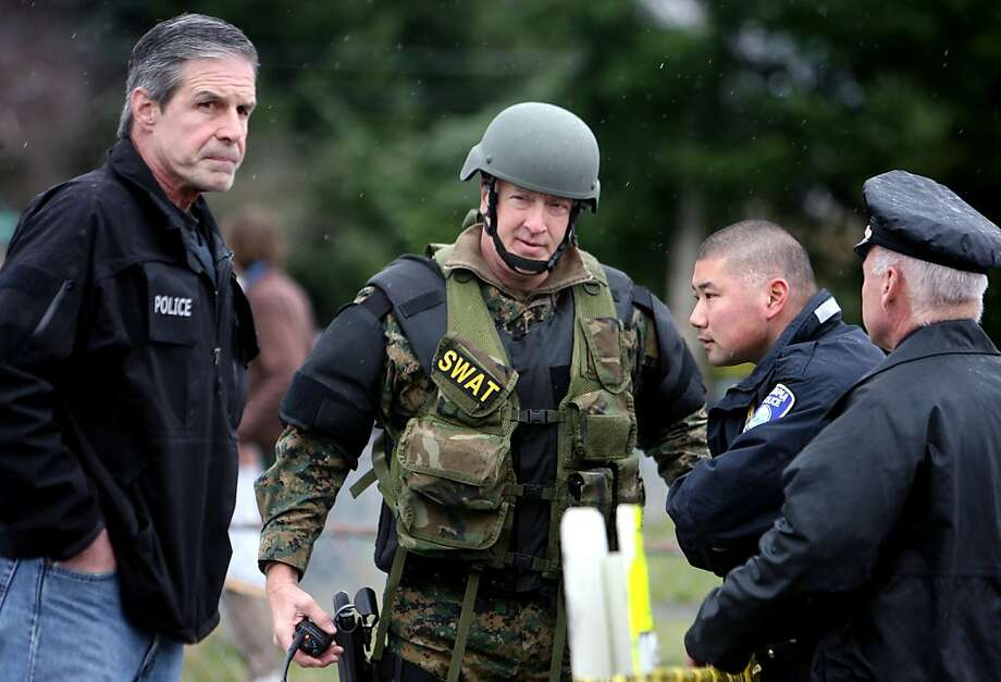 A member of the Thurston County SWAT Team talks with Olympia Police staff including Lt. Jim Costa, left, shortly before arresting Steven Daniel Kravetz, Saturday, March 10, 2012, in Olympia, Wash. Kravetz is accused of stabbing a judge and shooting a sheriff's deputy in a courthouse struggle on Friday. (AP Photo/The Olympian, Steve Bloom) Photo: Steve Bloom, Associated Press