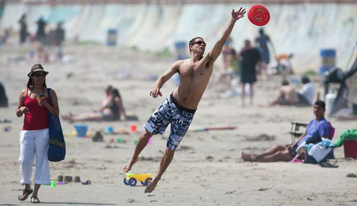 Josh Leuchtag of Houston reaches for a Frisbee on the beach in Galveston in March 2012.